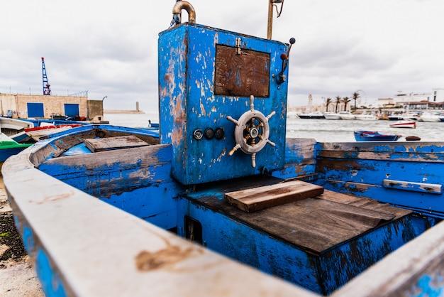 Pequeño timón de madera de un barco varado envejecido y abandonado en la orilla del mar.