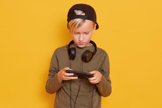 Pequeño tipo concentrado con camisa y gorra casual, jugando videojuegos en línea usando un teléfono móvil, posando con auriculares