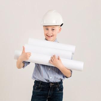 Pequeño trabajador de la construcción que muestra los pulgares para arriba