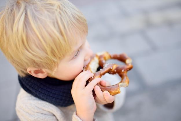 Pequeño turista comiendo pan bávaro tradicional llamado pretzel.