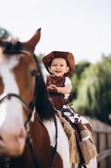 Pequeño vaquero sentado en un caballo