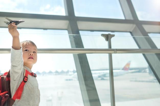 Pequeño viajero, niño asiático divirtiéndose jugando con avión