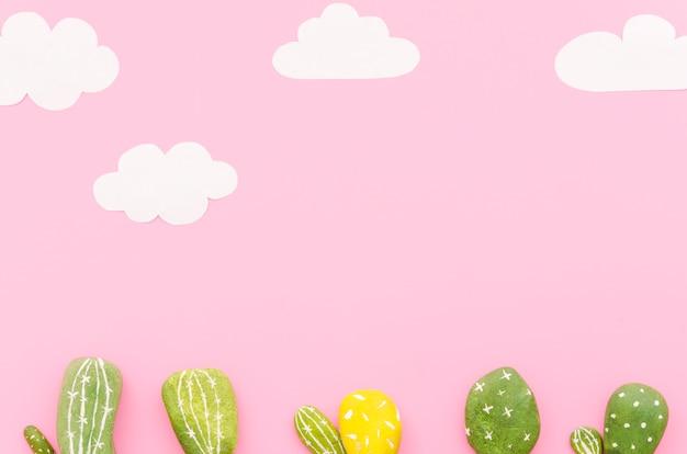 Pequeños cactus con nubes de papel sobre mesa.