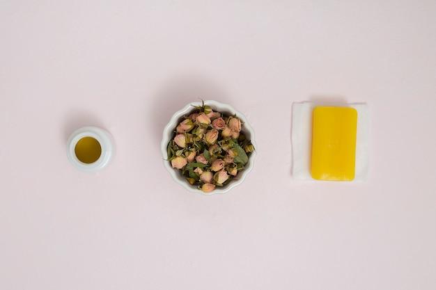 Pequeños capullos de rosas secos en un tazón de cerámica blanca; botella de miel y jabón amarillo a base de hierbas en una servilleta con fondo texturado