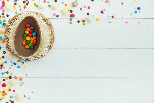 Pequeños caramelos en huevo de chocolate de pascua abierto en mesa