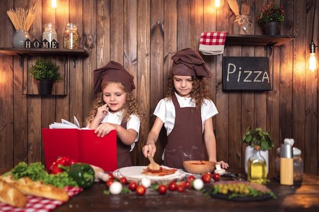 Pequeños cocineros leyendo el libro de recetas