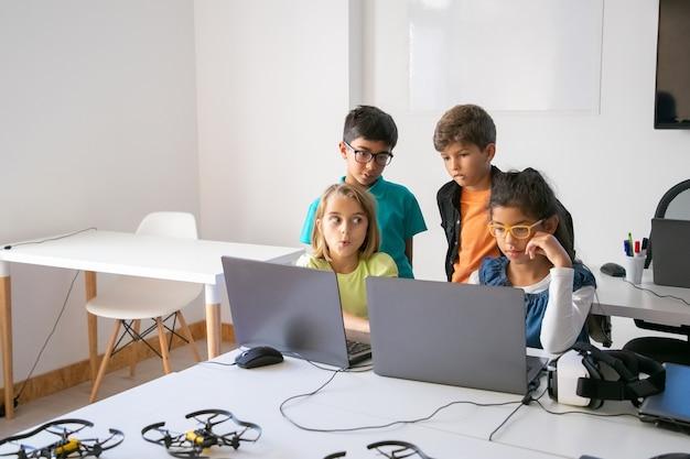 Pequeños compañeros de clase haciendo tareas grupales, usando computadoras portátiles y estudiando en la escuela de informática