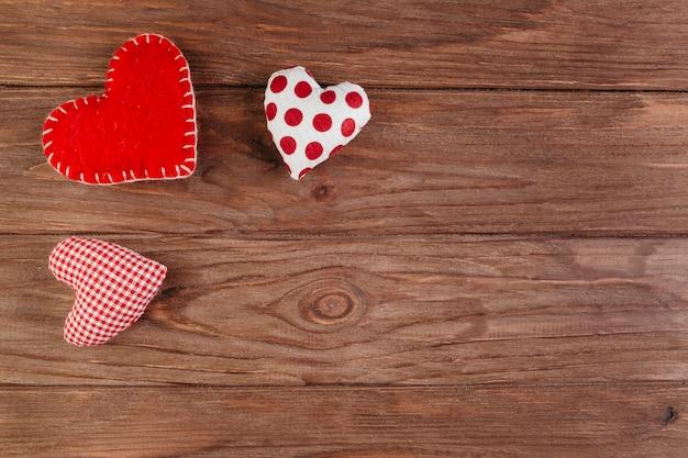 Pequeños corazones brillantes suaves en mesa marrón