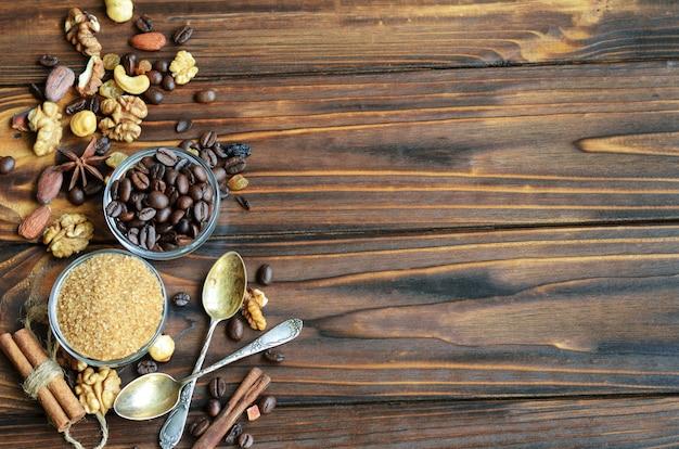 Pequeños cuencos de vidrio con azúcar moreno de caña y granos de café con ingredientes saludables como pasas, nueces y canela sobre fondo de madera natural