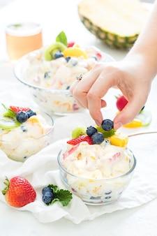 Pequeños cuencos de vidrio llenos de fruta y yogurt cremoso y sabroso