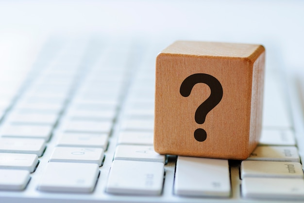 Pequeños dados de madera con signo de interrogación en el teclado