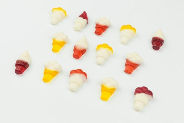 Pequeños dulces en forma de helado sobre fondo blanco