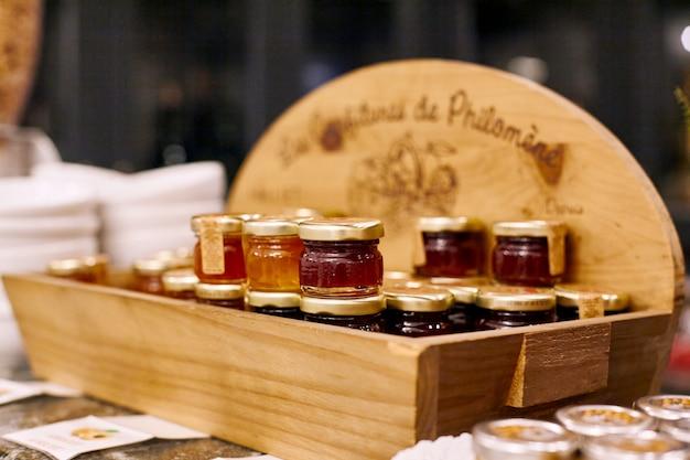 Pequeños frascos de mermelada de frutas coloridas se colocan en una caja de madera sobre la mesa