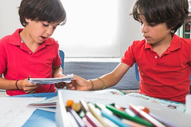 Pequeños gemelos haciendo artesanías de papel juntos Foto gratis