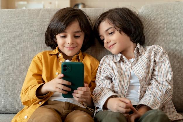 Pequeños gemelos jugando en un teléfono inteligente