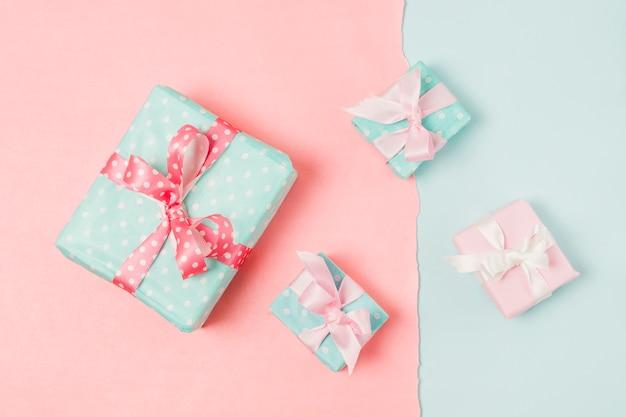 Pequeños y grandes regalos decorados en caja, atados con cinta, en papel tapiz azul y melocotón.