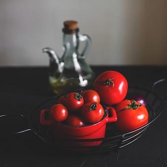 Pequeños y grandes tomates maduros en jarrón de acero y maceta de cerámica roja