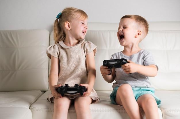Pequeños hermanos jugando juegos digitales con joystick