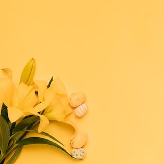 Pequeños huevos de pascua con hermosas flores de lirio amarillo sobre fondo amarillo