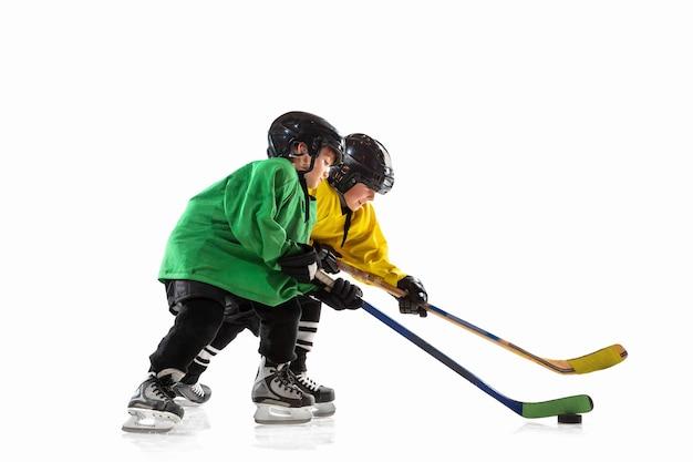 Pequeños jugadores de hockey con los palos en la cancha de hielo y fondo blanco.