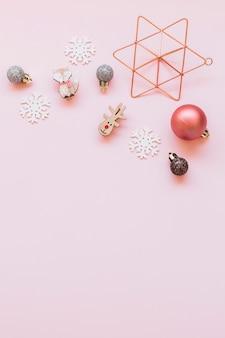 Pequeños juguetes navideños en mesa rosa.
