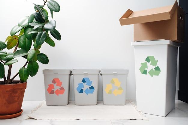 Pequeños y lindos contenedores de reciclaje en la mesa con flechas de diferentes colores. vista frontal.