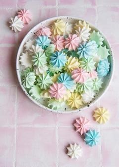 Pequeños merengues de colores en el cuenco de cerámica sobre fondo de mosaico rosa