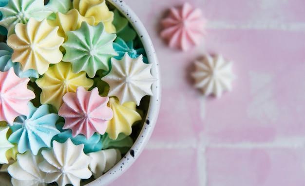 Pequeños merengues de colores en la placa de cerámica sobre fondo de mosaico rosa