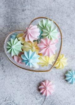 Pequeños merengues de colores en el recipiente en forma de corazón sobre fondo de hormigón