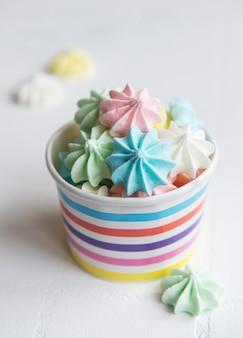 Pequeños merengues de colores en el recipiente de papel sobre fondo de mosaico