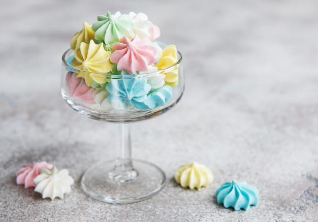Pequeños merengues de colores en el vaso sobre fondo de hormigón
