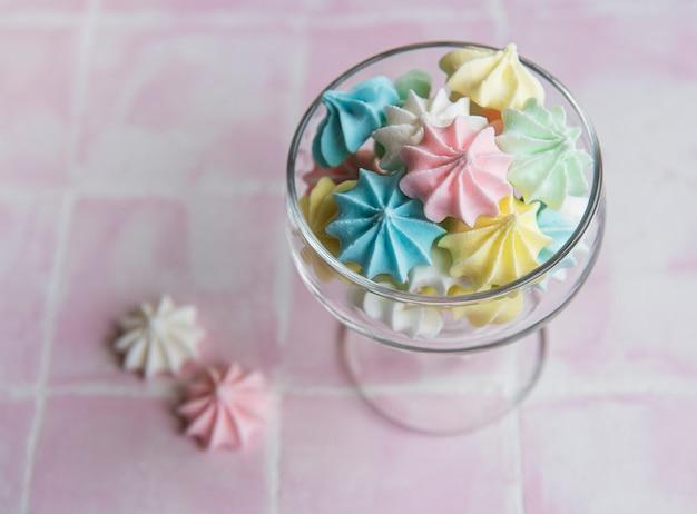 Pequeños merengues de colores en el vaso sobre fondo de mosaico rosa