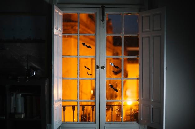 Pequeños murciélagos de papel de halloween en la ventana de la habitación