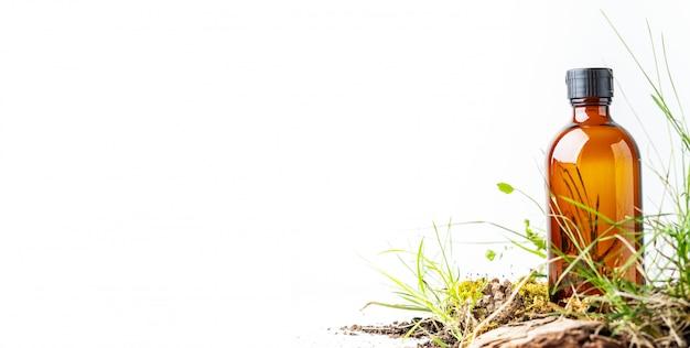 Pequeños musgos y hierba de productos cosméticos orgánicos en frasco de vidrio marrón