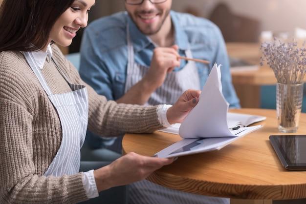 Pequeños negocios. encantado y satisfecho par de propietarios de cafés sonriendo y trabajando con papeles mientras están sentados junto a la mesa