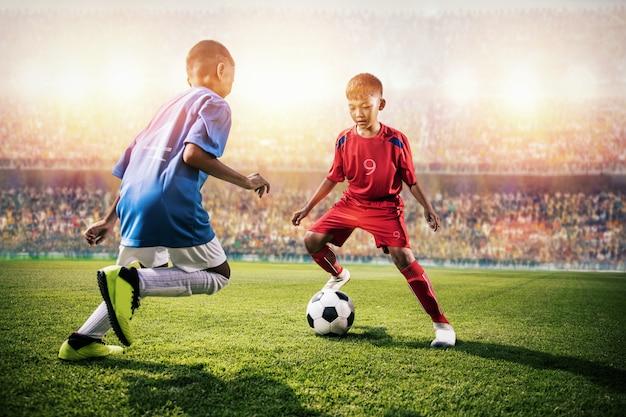 Pequeños niños asiáticos de fútbol en acción en el estadio