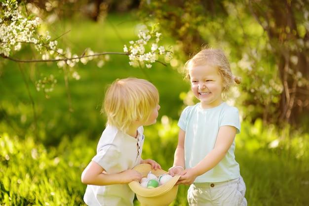 Los pequeños niños encantadores buscan huevos pintados en el parque de la primavera el día de pascua.