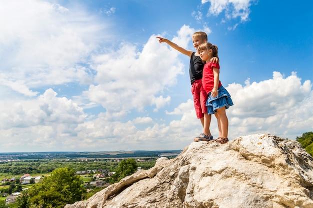 Pequeños niños niño y niña de pie en la roca de la montaña y mirando hacia el futuro. niño mostrando con su mano