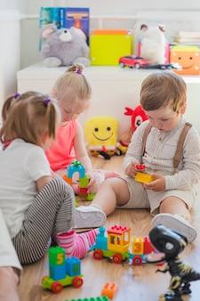 Pequeños niños sentados en el suelo jugando