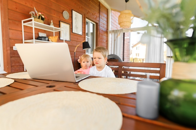 Pequeños niños sonrientes, hermano y hermana, ríen y juegan con la computadora portátil, se comunican por videoconferencia en el chat. interior casero espacioso y acogedor.