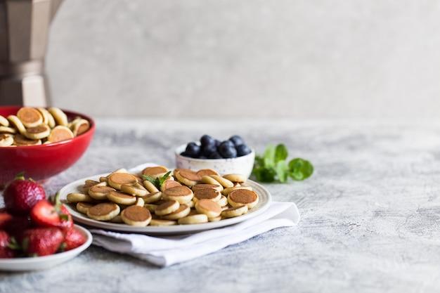 Pequeños panqueques para el desayuno. tortitas de cereales con arándanos, plátanos, fresas sobre fondo gris.