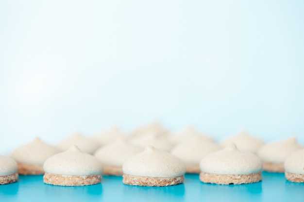 Pequeños pasteles blancos sobre fondo azul