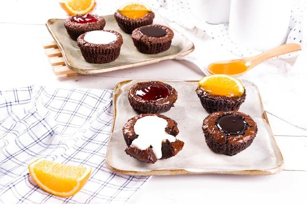 Pequeños pasteles de chocolate con salsa de leche, fresa, chocolate y naranja sobre fondo de mesa de madera blanca.