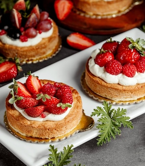 Pequeños pasteles decorados con crema de fresa y frambuesas