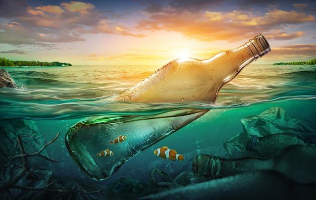 Pequeños peces en una botella entre la contaminación del océano.