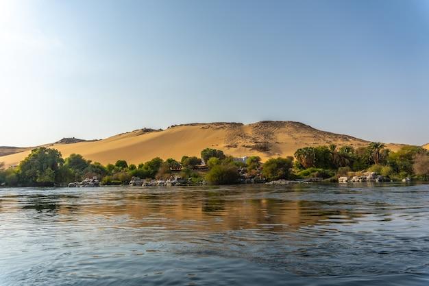 Pequeños pueblos y templos antiguos navegando por el río nilo en la ciudad de asuán. egipto