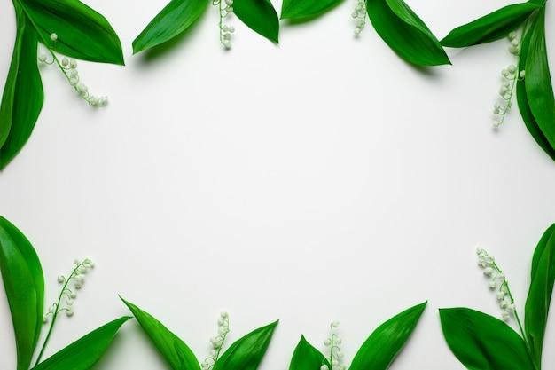 Pequeños ramos de lirio de los valles como un marco floral con espacio de copia plano sentar con fondo blanco.