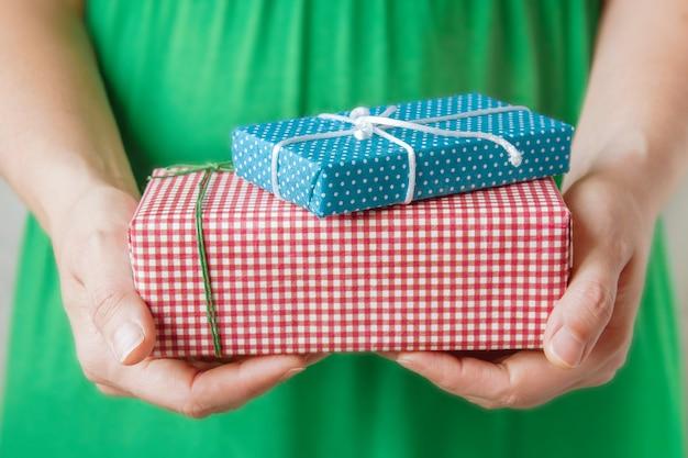 Pequeños regalos en manos de mujer. concepto de navidad.