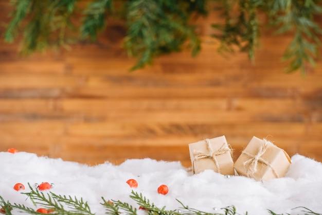 Pequeños regalos en la nieve con ramas de coníferas.