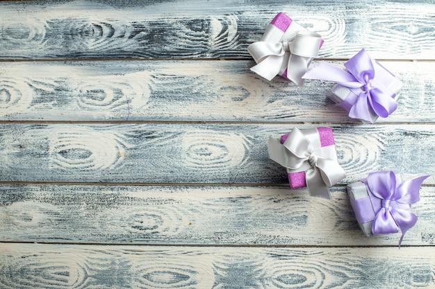Pequeños regalos de vista superior en superficie de madera